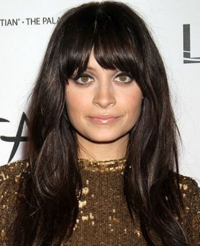 Thick bangs and long hair with moderate volume elongate a round face